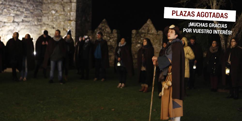 Un actor caracterizado de peregrino dirige al grupo en la visita teatralizada nocturna al castillo de Monterrei