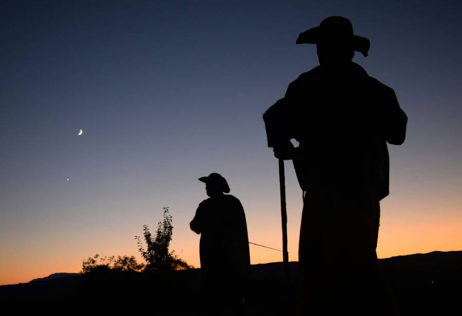 Figuras recortadas de un peregrino y un soldado de la guardia del siglo XVII sobre el cielo nocturno en una visita teatralizada al castillo de Monterrei (Ourense)