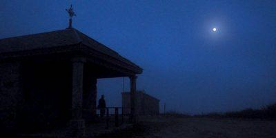Se vislumbra a la luz de la luna la silueta de la capilla del alto de San Mamede y junto a ella una persona que mira al cielo nocturno