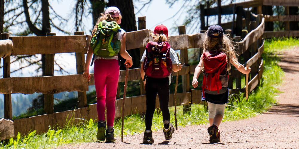 Un grupo de niñas hace senderismo por un camino soleado