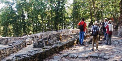 Un grupo de personas realiza una visita guiada entre los muros de piedra del lugar arqueológico de Armea, rodeados por carballos jóvenes, en Allariz (Ourense)